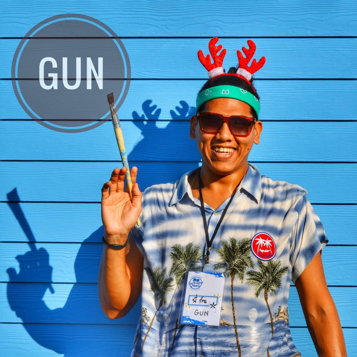 Man wearing colourful shirt wearing red Christmas antlers holding paint brush stood in front of bright blue backdrop