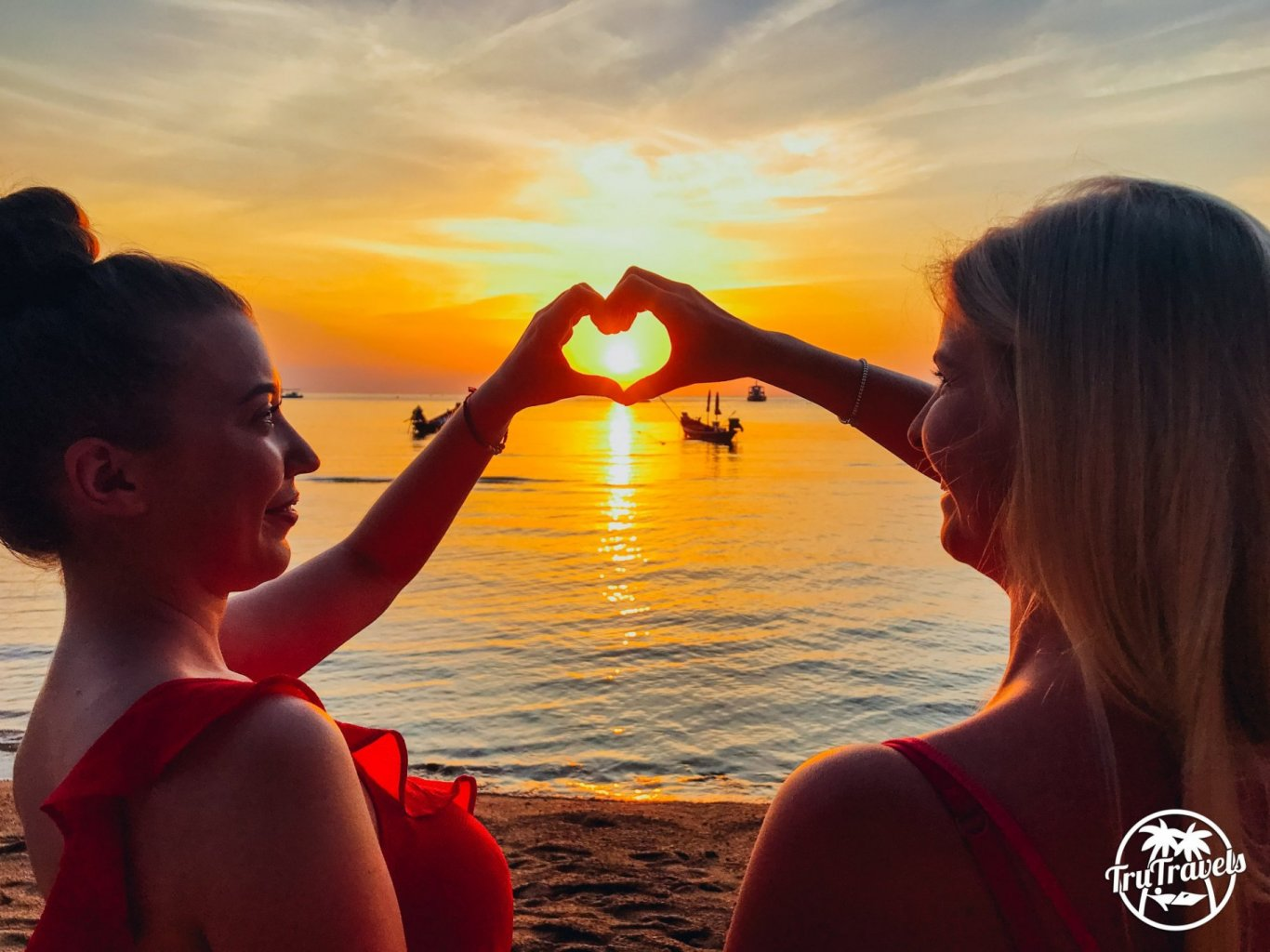 Girls on the beach, sunset with heart hands