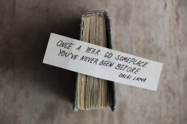 A photo of a book with a quote ''Once A Year Go Somewhere You've Never Been Before'' by Dalai Lama