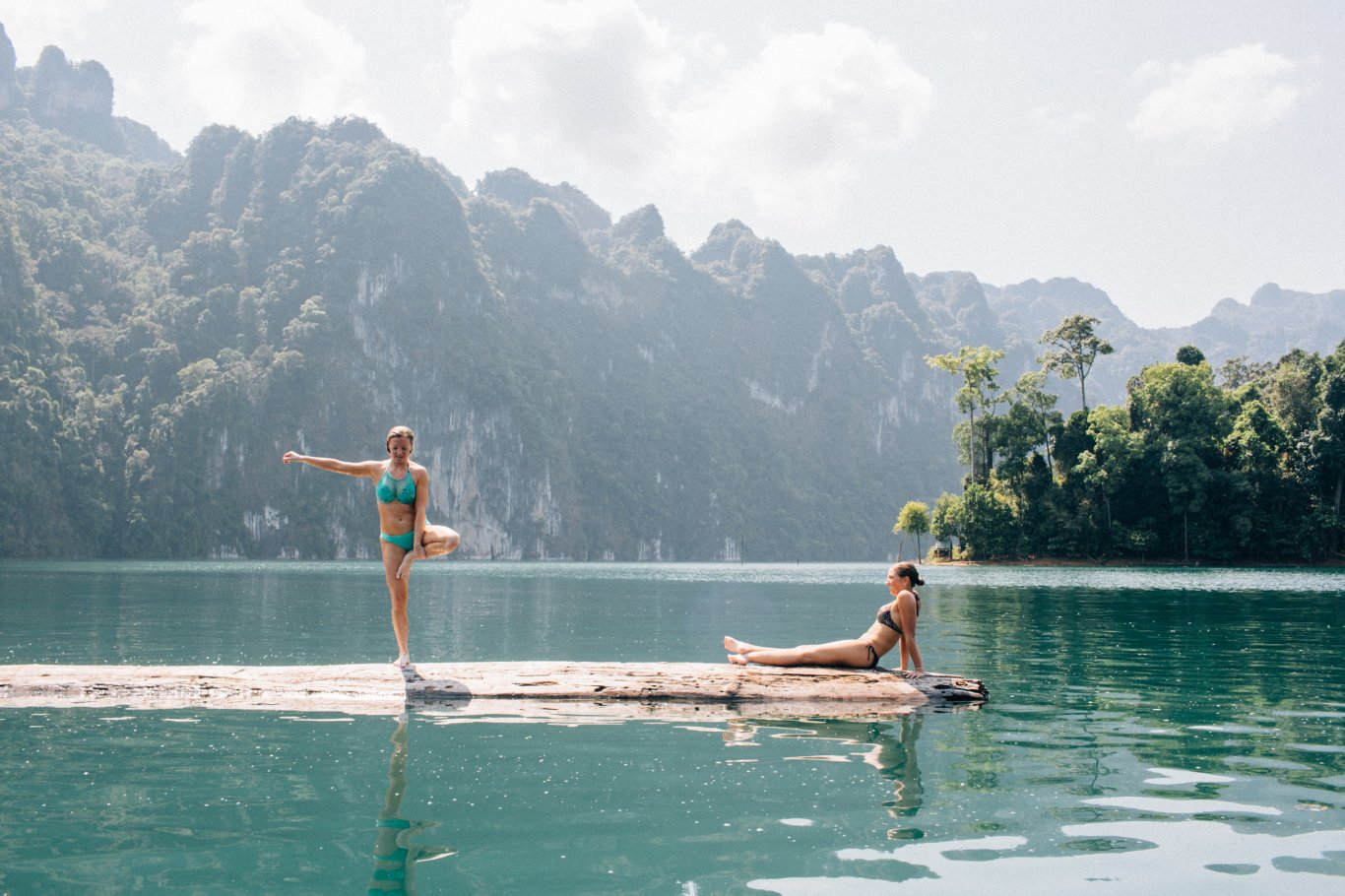 Two girls on the log in the middle of the lake at Khao Sok National park in Thailand