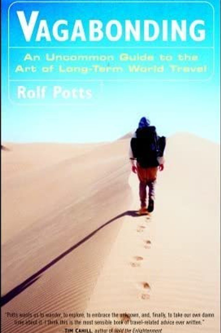 Vagabonding book cover - man walking across sand dunes with blue sky
