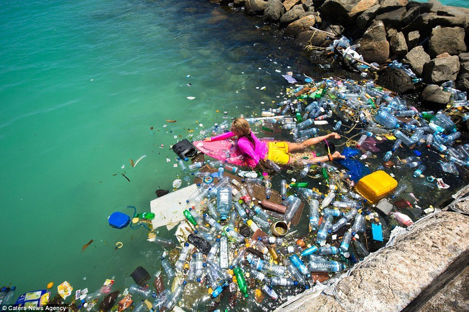 girl swimming in the sea surrounded ocean plastic / waste