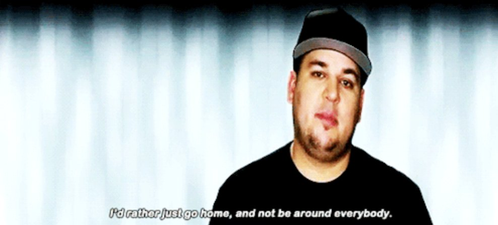 Rob Kardashian sitting in front of blank wall wearing Hat looking sad