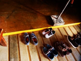 A photo of five pairs of shoes on wooden decking