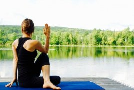 A women practicing yoga by a serene lake