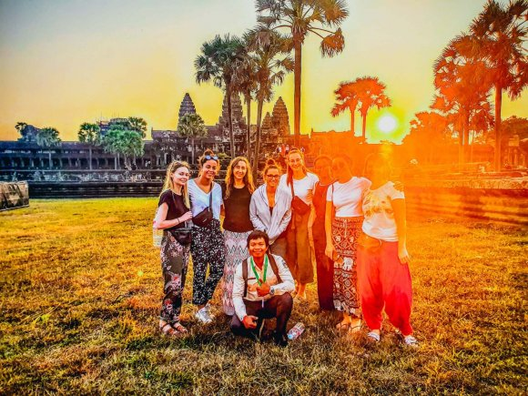 Group of Young Travellers in front of Angkor Wat Temple in Cambodia at Sunrise with Palm Trees