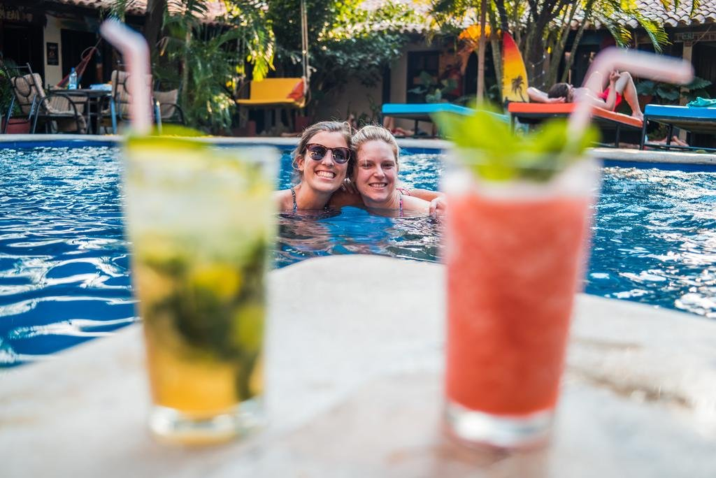 2 friends in a swimming pool with a drink