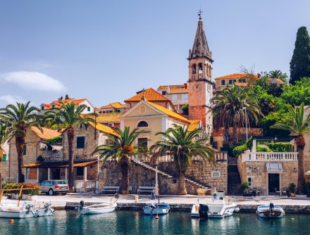 The island of Brac in Croatia showing the incredible architecture, palm trees along the waterfront and boats on the water