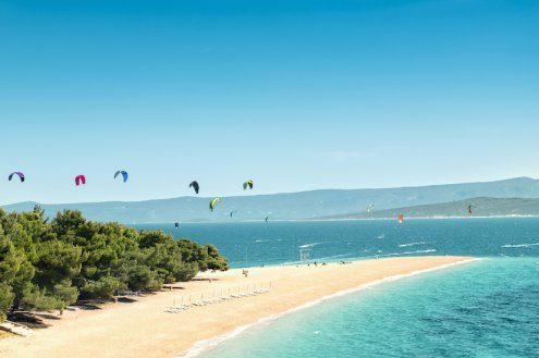 A beach on the island of Brac, Croatia with bright clear blue water and white sandy beach with kite surfing in the background