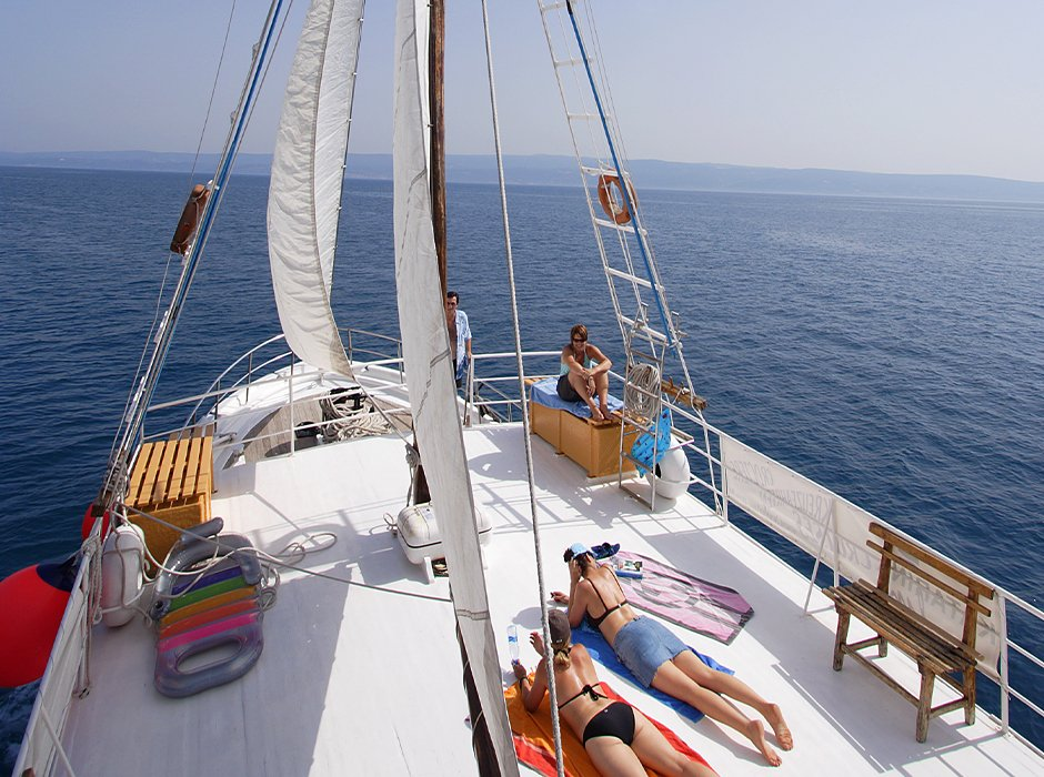 A view of the top deck on the sail boat in Croatia, showing guests tanning