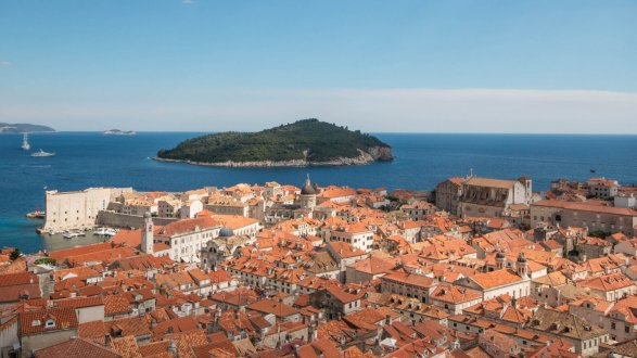 An aerial view of Dubrovnik, Croatia's terracotta architecture and landscape with an island in view.