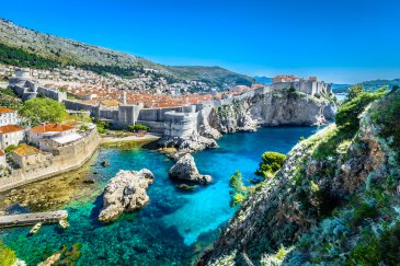 A aerial view of Dubrovnik, Croatia showing bright clear blue water, the historical sea walls and luscious greenery surrounding Croatia