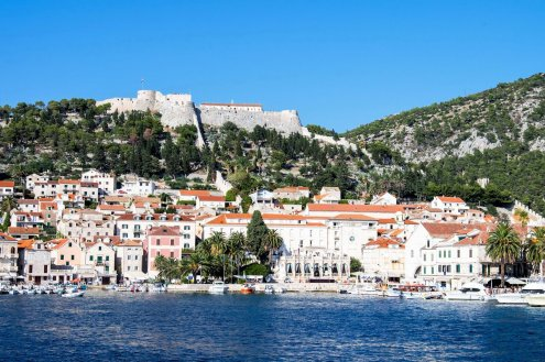 The well-known island of Hvar, with deep blue water, white houses and lush green hills with a view of the Hvar fortress.