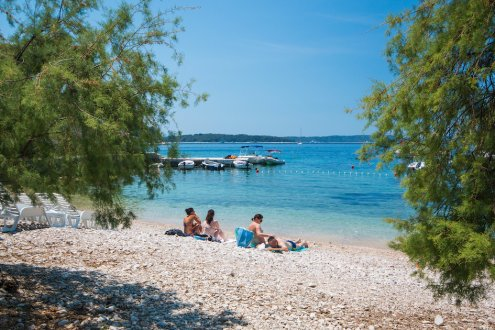 A secluded stunning beach on the island of Hvar, Croatia with bright blue clear water and visitors enjoying the sunshine