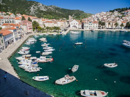 A stunning photo of the island, Hvar, Croatia showing boats on the bright turquoise water , the town and surrounding mountains