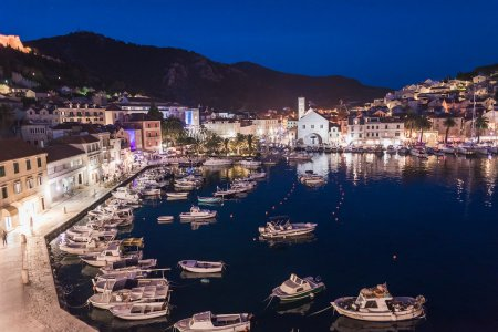 The marina in Hvar, Croatia at night showing bright lights from the town and mountains in the background