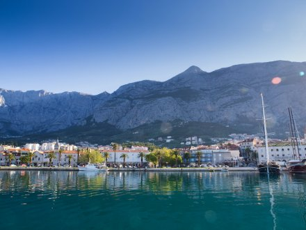 A shot of the port town of Makarska, Croatia showing the amazing surrounding mountains, bright blue water and houses along the waterfront.