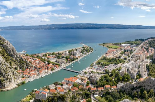 An aerial view of Omis in Croatia, showing the lush green landscape and the town