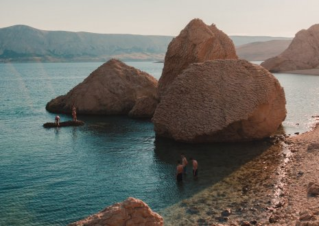 A picturesque shot of Pag island in Croatia, showing a few visitors exploring the waters.