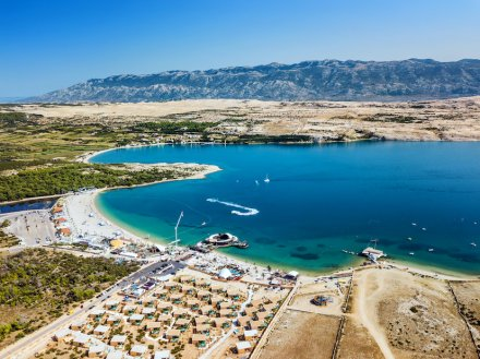 An aerial shot of Pag island in Croatia, showing mountains in the distance, the different shades of blue in the sea, and the town/harbour.