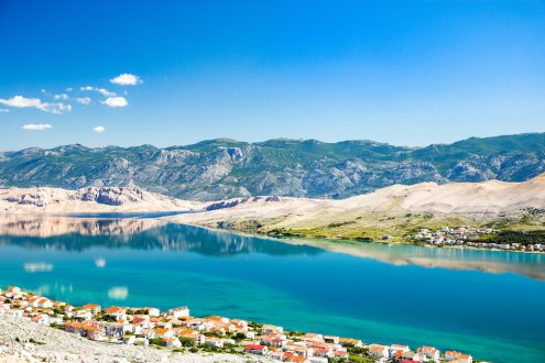A breathtaking photo of Pag island, Croatia showing the amazing surrounding landscapes, bright turquoise waters and houses of the island.