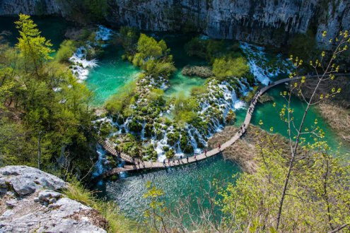 A stunning birds eye view shot of Plitvice falls, showing the bright clear turquoise water and trees at this national park in Croatia