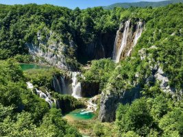 A gorgeous photo of the Plitvice falls in Croatia, showing the lush greenery of the national park and the bright turquoise waters.