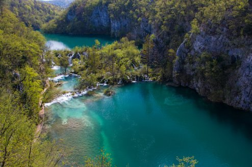 A breathtaking photo of Plitvice waterfalls showing still turquoise waters and the luscious greenery surrounding the water in Croatia.
