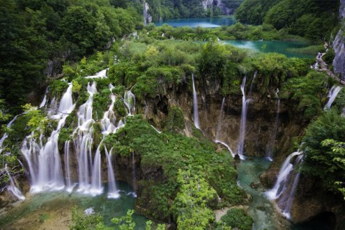 A stunning aerial shot of the falls at Plitvice National park in Croatia, showing the turquoise water and lush greenery.