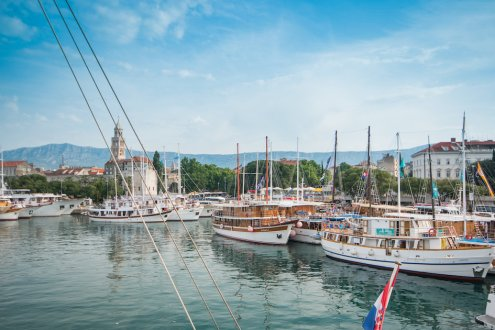 The marina in Split, Croatia, showing boats on the water and the mountain landscape in the background