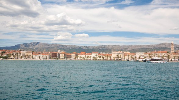 A photo of Split, Croatia from the sea showing the town and the mountain landscapes in the background