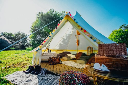 Large Teepee Glamping tent in open field with two beds and picnic table set