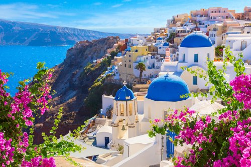 A scenic view of the white villas in Santorini from behind pink flowers with the mountains and sea in the background