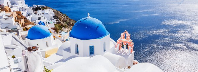 View of the tops of the white and blue villas in Santorini with the blue ocean in the background