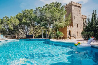 Small Spanish Castle with large Pool with floating inflatable unicorn lush Trees and blue sky