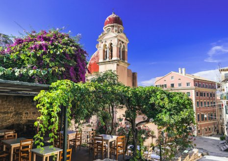 A scenic photo of Corfu town in Greece, with blue skies and a lush balcony surrounded by greenery