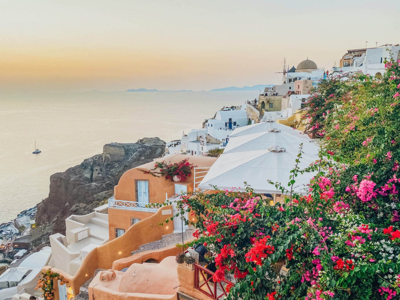 A photo of the sunset in Oia, Santorini, Greece with red and pink flowers in view