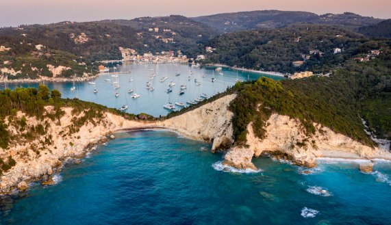 A stunning aerial view of the coast at sunset with bright blue water in Lakka, Paxos, Greece