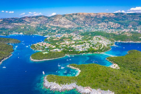Aerial view of Syvota, Greece with different shades of blue in the sea, the town in the distance and lush green landscapes