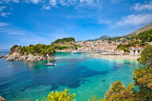 A scenic view of the coast, bright clear blue water and houses along the waterfront in Syvota, Greece
