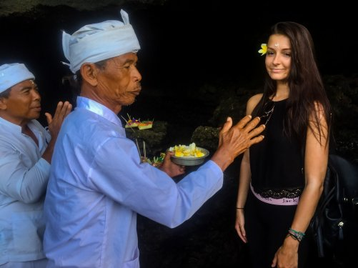 Local Balinese man giving flower to girl