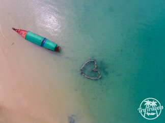 Birds eye view of blue sea, boat and people in love heart shape