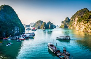 View of boats at sea with rock islands in the distance - Ha long Bay