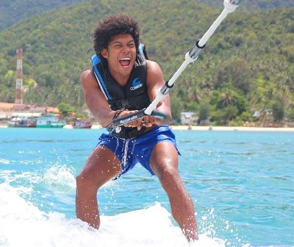 Man wake boarding surrounded by blue sea and green hills