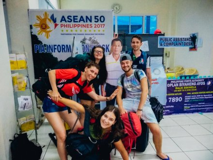 Group pf travellers smiling in airport in the Philippines