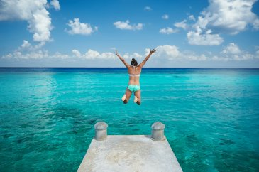 A girl jumping into the clear blue ocean