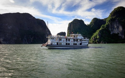 The boat cruising along Halong Bay during the day in Vietnam
