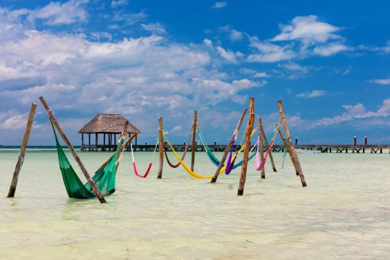 colourful sea hammocks, hut in distance and blue sky