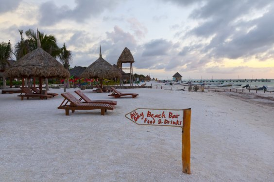 Beach, with sunbeds and sign saying beach bar food and drinks