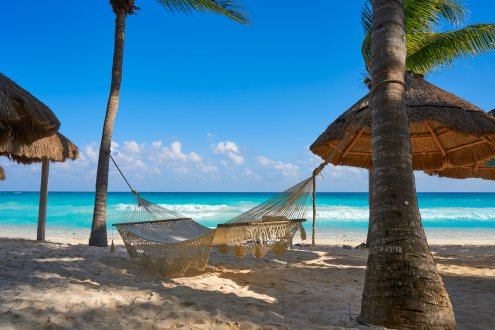Hammock on beach with blue sea and sky behind